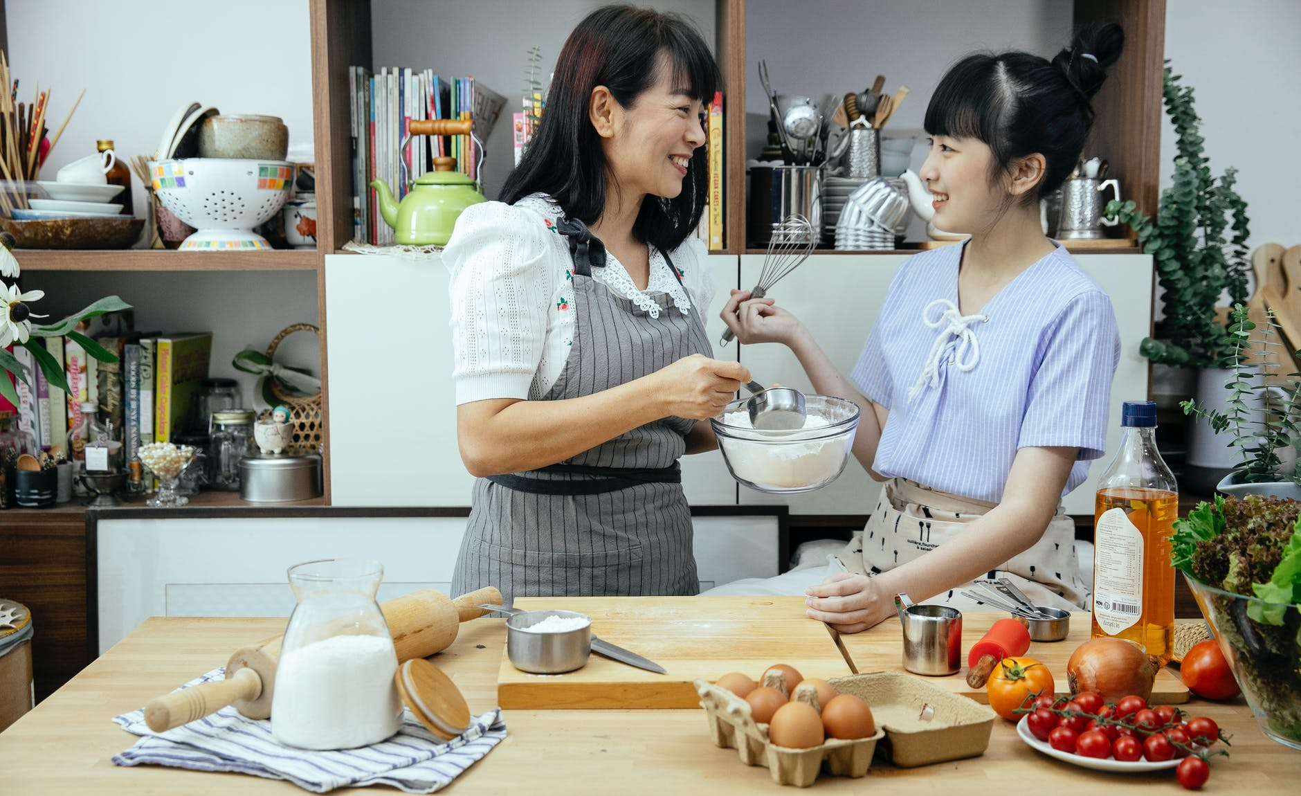 happy asian daughter and mother discussing recipe in kitchen